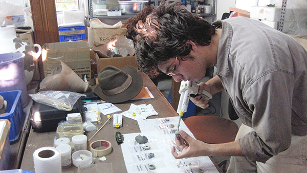 Geoffrey Ludvik (B.A.'13, Anthropology and Classical Humanities) makes putty impressions of artifacts at Troy in 2011 to prepare for study on a scanning electron microscope. (Photo courtesy William Aylward)