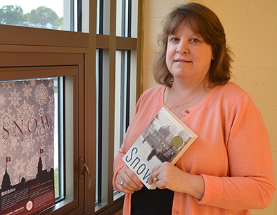 Denise Beasley, an English teacher at Osseo-Fairchild High School who is shown holding a copy of Snow by Orhan Pamuk, has utilized the Great World Texts program for five years. (Scott Schultz)