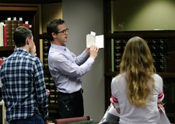 Assistant Professor of English Joshua Calhoun shows students from a rare book from Memorial Library's Department of Special Collections. (Photo by Kevin Boettcher, Department of English)