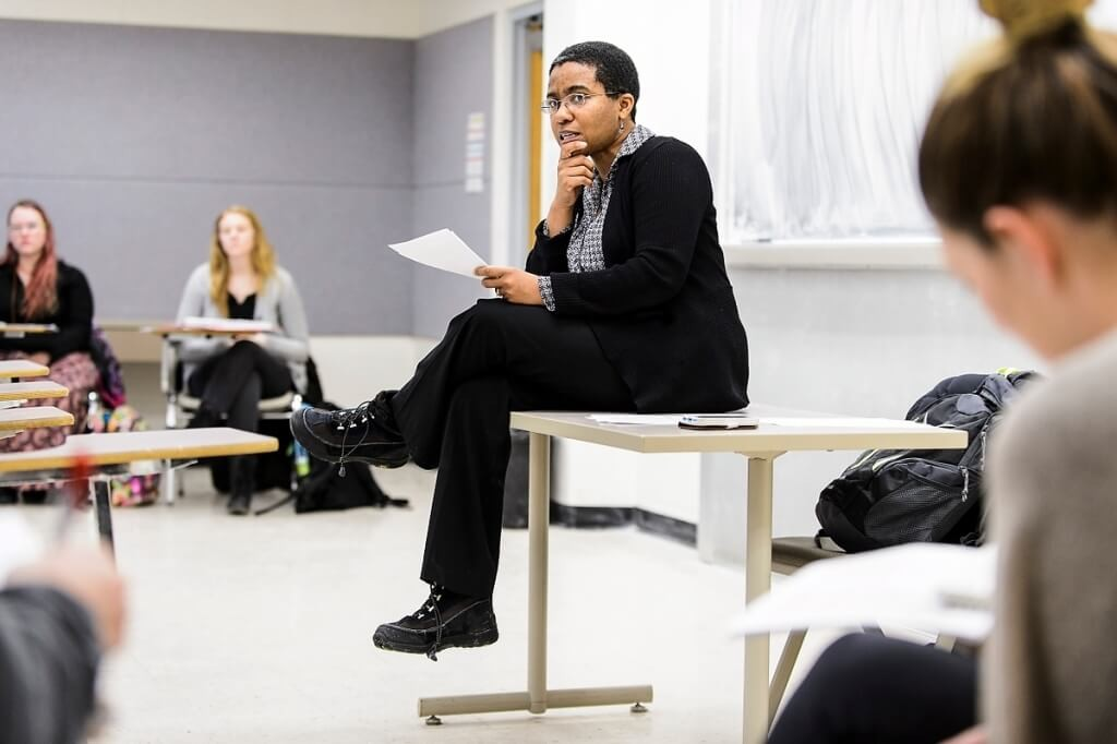 Keisha Lindsay sits on a table as she teaches a class of undergraduate students